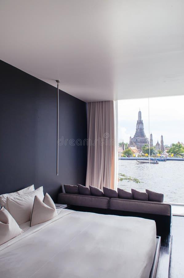 Sovrummet med vit säng för den svarta väggen, kuddar uttrycker, lampan Fjärdvind royaltyfri foto