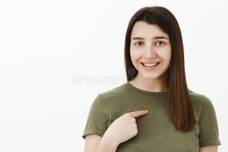 Soy lo que usted necesita Amistoso-mirada muchacha morena brillante joven ambiciosa y confiada en 20s que lleva la camiseta verde fotos de archivo