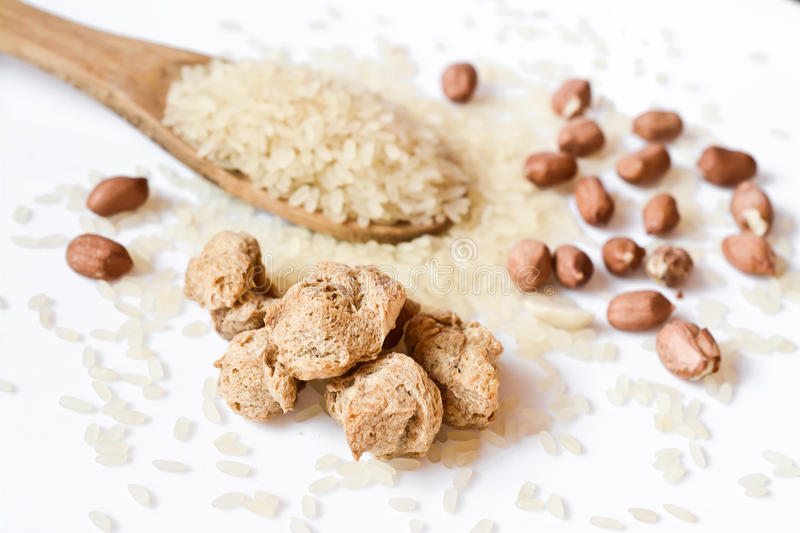 soy meat and a spoon with uncooked rice close-up, studio shot on white royalty free stock photos