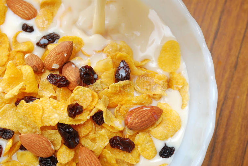 Soya milk pouring into healthy cereal stock image