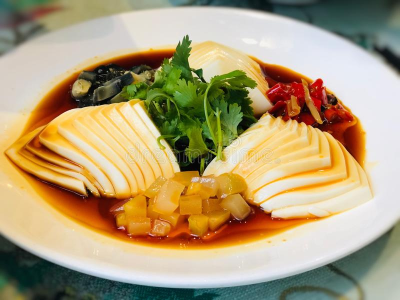 Soybean curds or tofu egg sliced into pieces in a white plate, eat with pickled cucumbers, chili, pickled ginger. royalty free stock photo