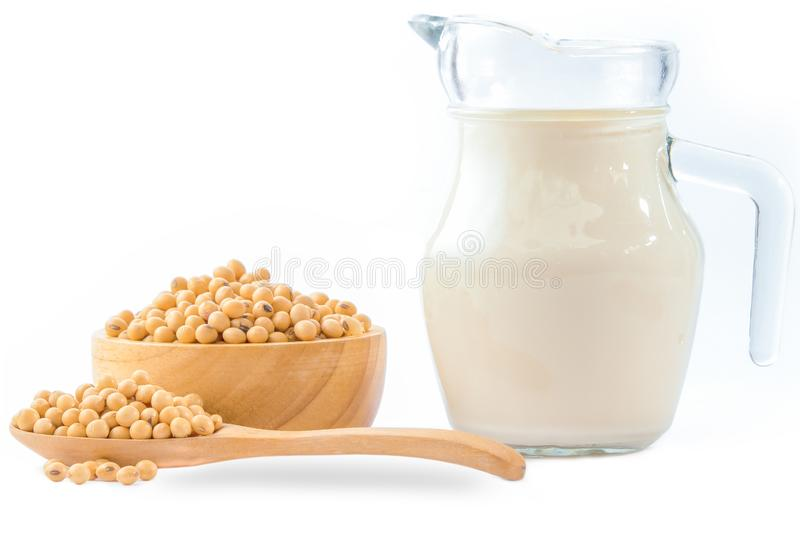 Soybeans and soy milk in a glass isolated. On white background. soy beans in wooden bowl and spoon royalty free stock images