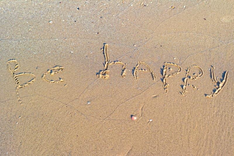 Soyez heureux écrit dans le sable image stock