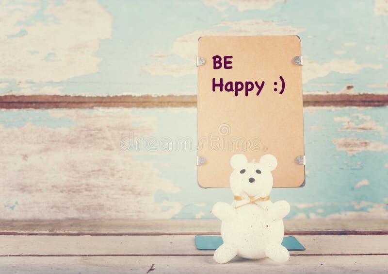 Soyez heureux a écrit le support de papier et mignon concernez b en bois bleu grunge photo stock