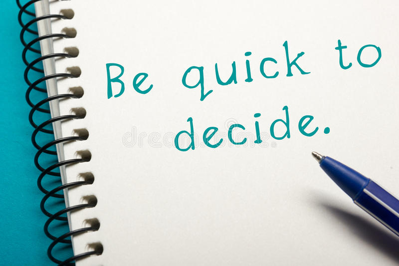 Soyez rapide pour décider - la vue supérieure de table de bureau Bloc-notes avec le texte et le stylo images stock