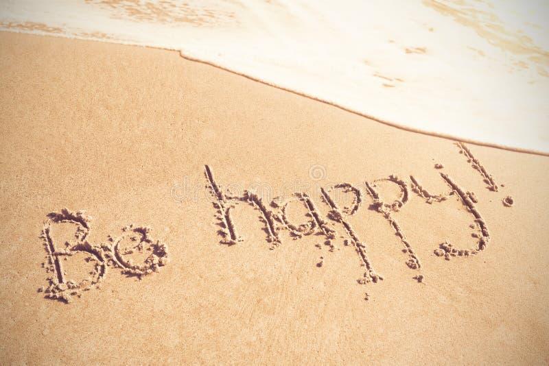 Soyez texte heureux écrit sur le sable image stock