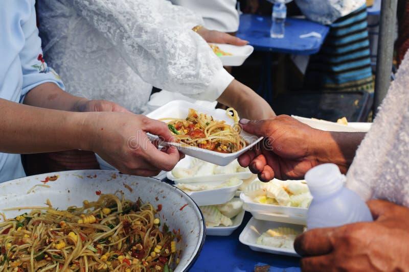 Sozialprobleme der Armut geholfen durch die F?tterung: Freiwilliger, zum das hungrige in der Gesellschaft einzuziehen: Das Konzep lizenzfreie stockbilder
