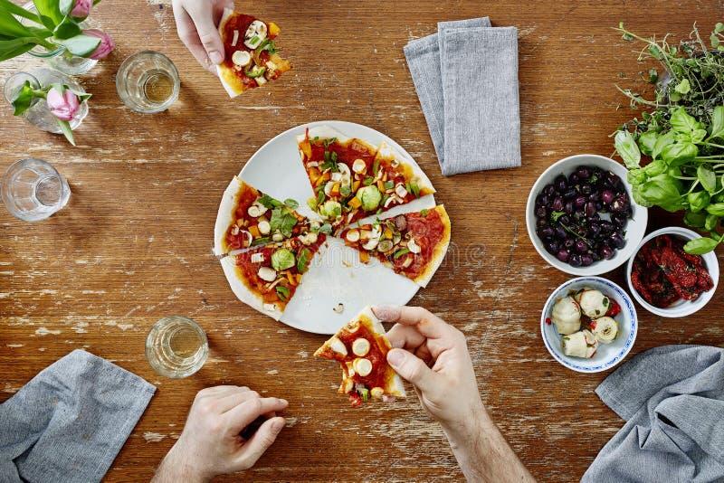 Sozialtreffen an peoplehaving Pizza des Abendessens zwei und an trinkendem Wein stockfotos