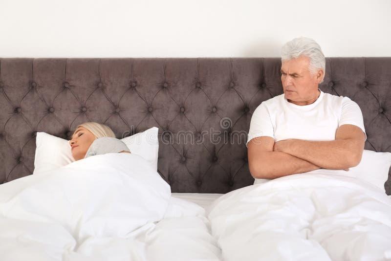 Spęczenie mężczyzny dojrzały obsiadanie na łóżku blisko jego sypialnej żony w domu obraz royalty free