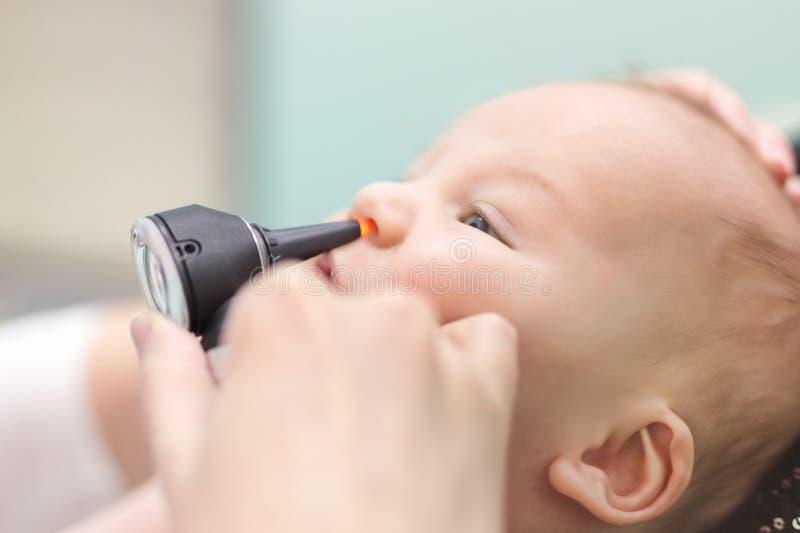 Spädbarn i pediatrisk klinik Handen för närbilddoktors` s med den moderna otoscopen som undersöker, behandla som ett barn näsan f arkivfoton