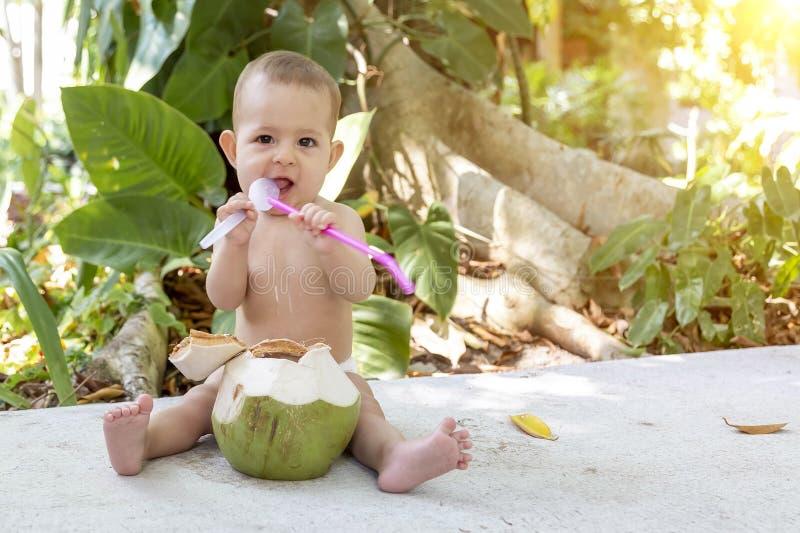 Spädbarn med spolning och salivavsöndring på tropisk semester Ät och drycker, grönt kokosnöt Sits på marken och gnaga en sked royaltyfria foton