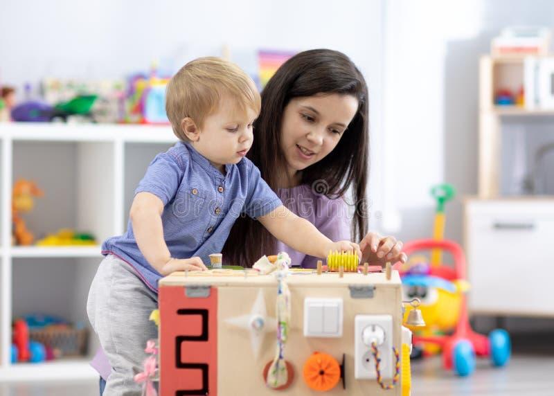 Spädbarn som leker med bussbord Moderskolbarn i daghem eller på daghem arkivfoton