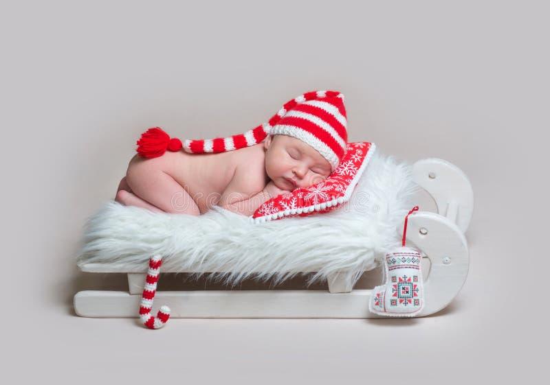 Spädbarnet behandla som ett barn att sova på trälathunden royaltyfria bilder