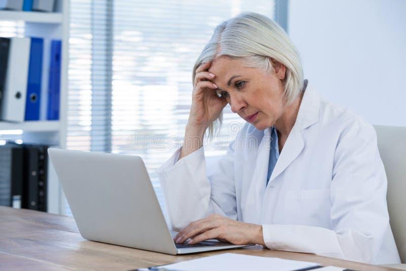 Spänd kvinnlig doktor som arbetar på hennes bärbar dator arkivfoton