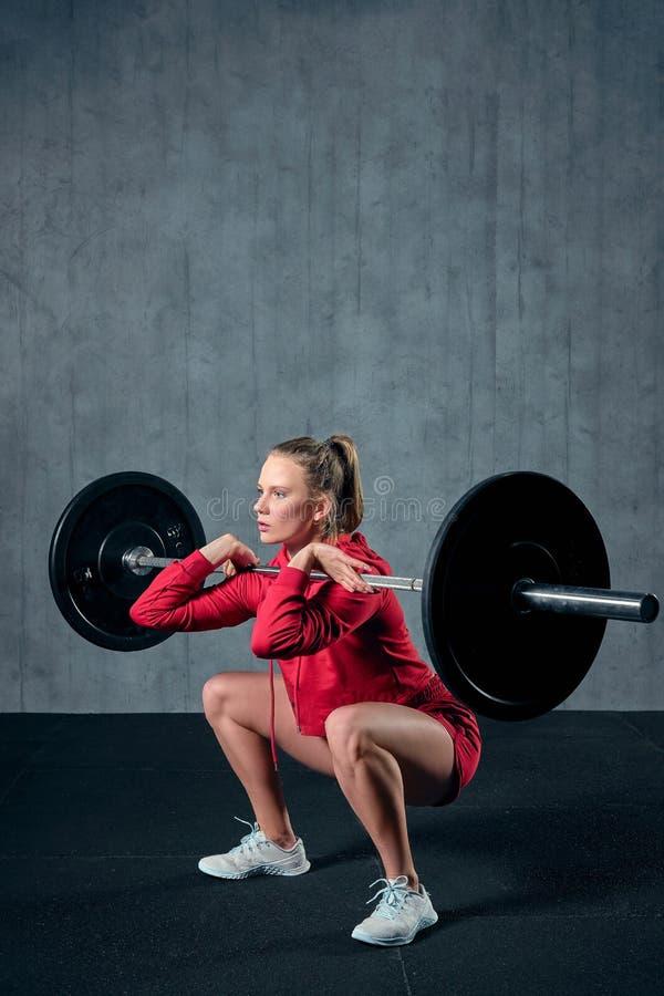 Spänd ung idrottskvinna som är klar att utföra skuldrapressövning med den tunga skivstången royaltyfria foton