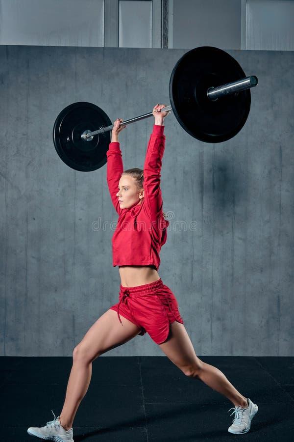 Spänd ung idrottskvinna som är klar att utföra skuldrapressövning med den tunga skivstången arkivbilder