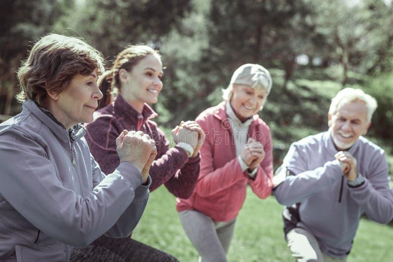 Spända sportive pensionärer som håller ögonen på på deras instruktör arkivfoton