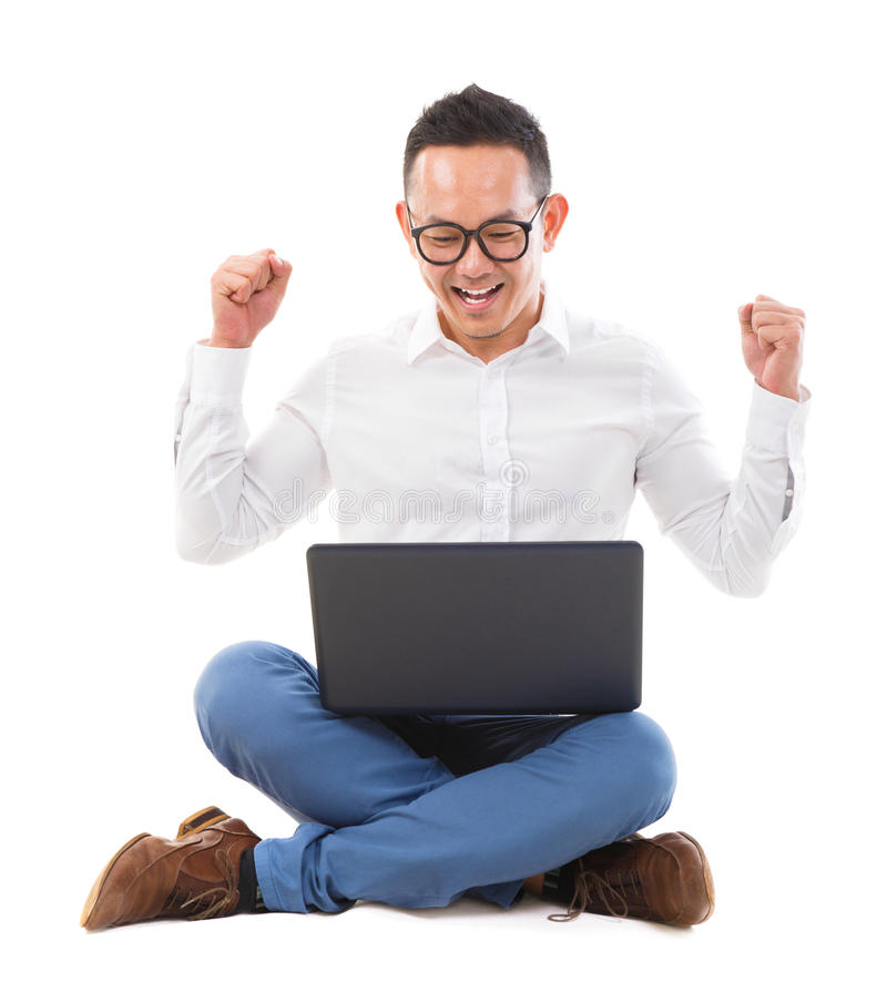 Spännande asiatisk man som använder bärbar dator arkivbilder