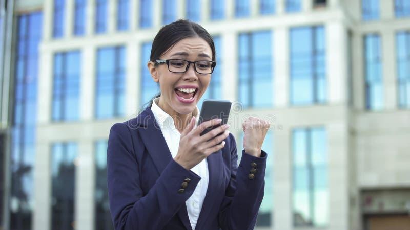 Spännande dam i dräkten som mottar goda nyheter som gör ja-gest, lyckad start arkivfoto
