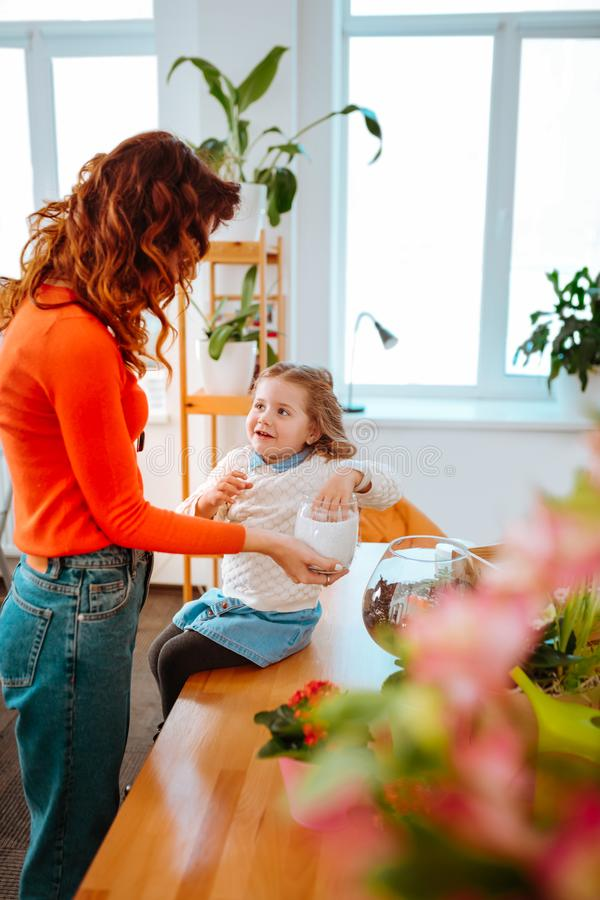 Spännande dotterkänsla, medan ta omsorg av växter med mamman arkivbilder