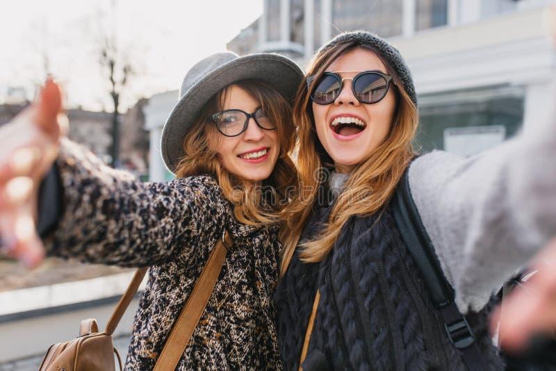 Spännande flickor i stilfulla exponeringsglas som har durning morgon för gyckel, går runt om stad Utomhus- stående av två glade v arkivfoto