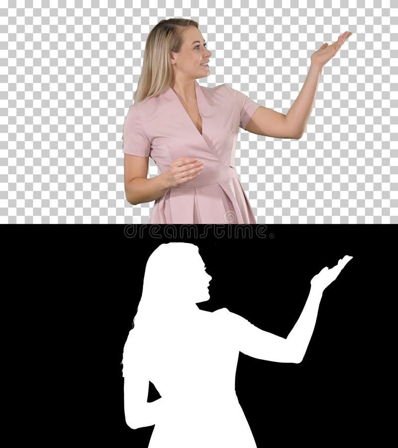 Spännande härlig ung kvinna i rosa klänning som talar till kameran, Alpha Channel arkivfoto