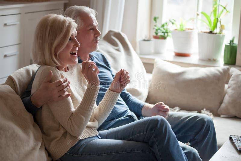 Spännande höga par kopplar av på hållande ögonen på TV för soffan royaltyfria bilder
