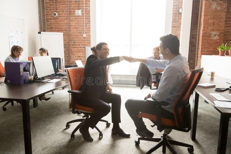 Spännande manliga kollegor ger nävar knuffar till i regeringsställning fotografering för bildbyråer