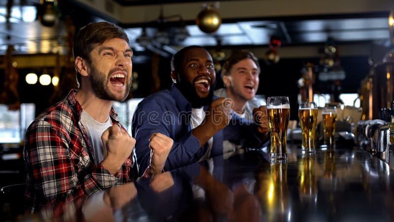 Spännande multietniska vänner som stöttar sportlaget, seger av landslaget royaltyfri foto