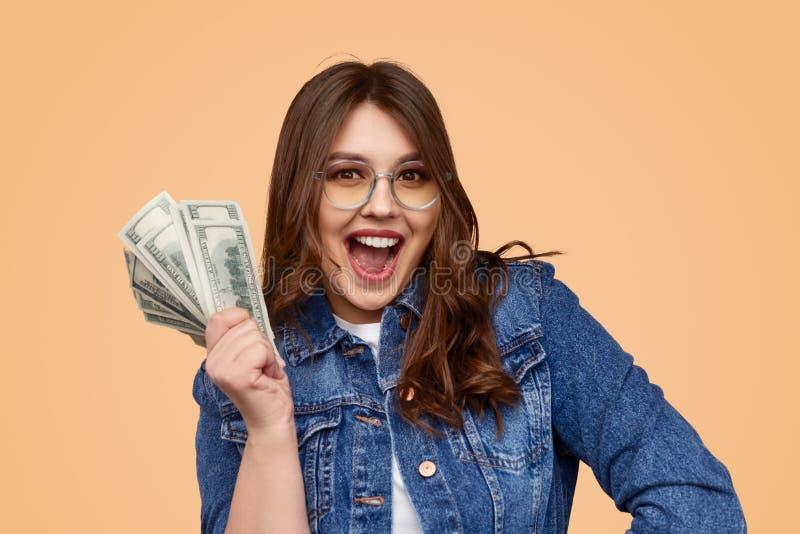Spännande plus formatkvinna med pengar arkivfoto