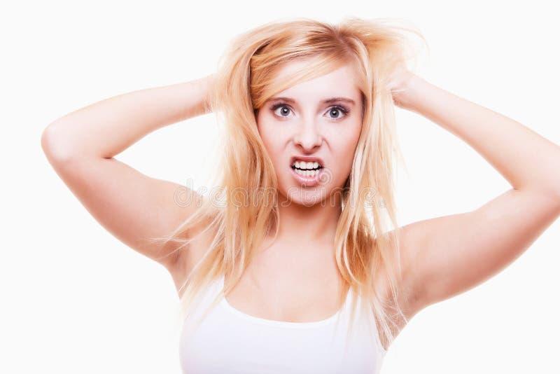 Spänning. Den unga kvinnan frustrerade att dra hennes hår på vit arkivbilder
