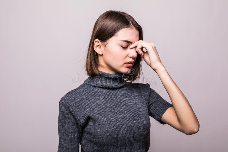 Spänning och huvudvärk Den unga kvinnan som har migrän, smärtar på grå färger royaltyfria bilder