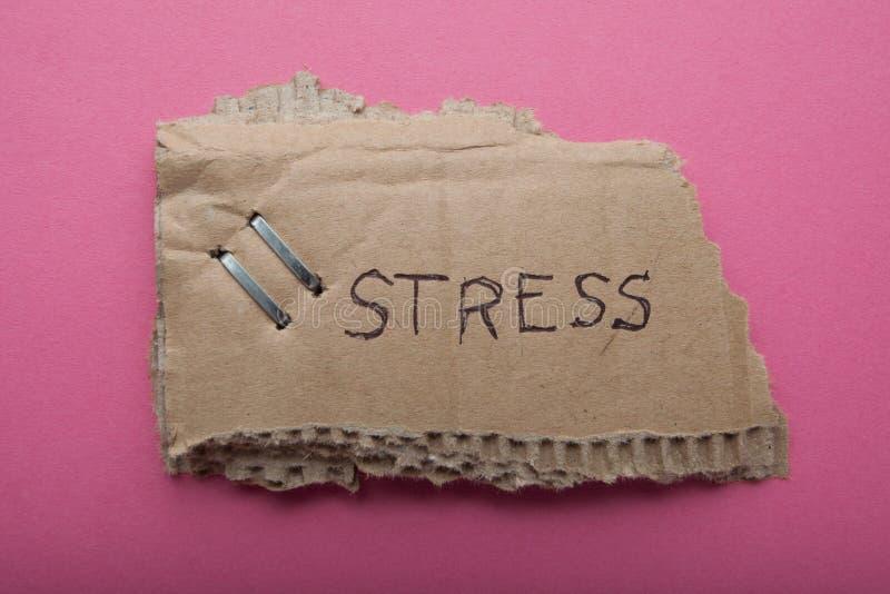 Spänningarna för ordet som 'är skriftliga på en gammal sönderriven papp, isoleras på en rosa bakgrund arkivfoton