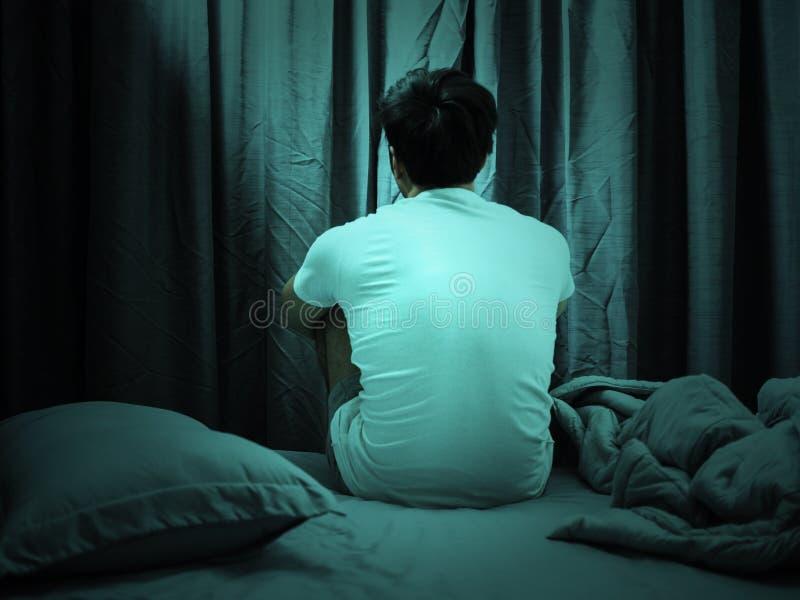 Spännings- och fördjupningsbegrepp, mansammanträde på säng, färgfilter arkivfoto