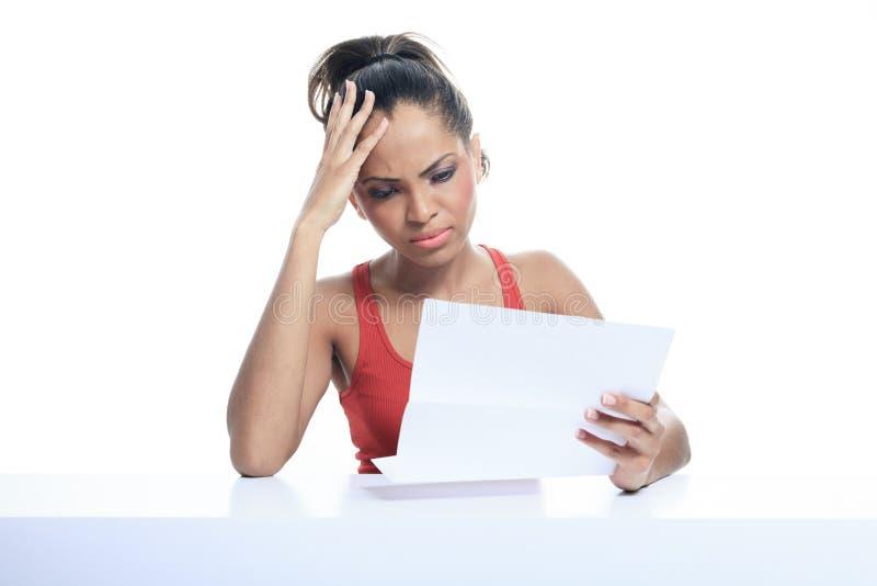 Spänningskvinna som betalar räkningar som isoleras på vit royaltyfri foto