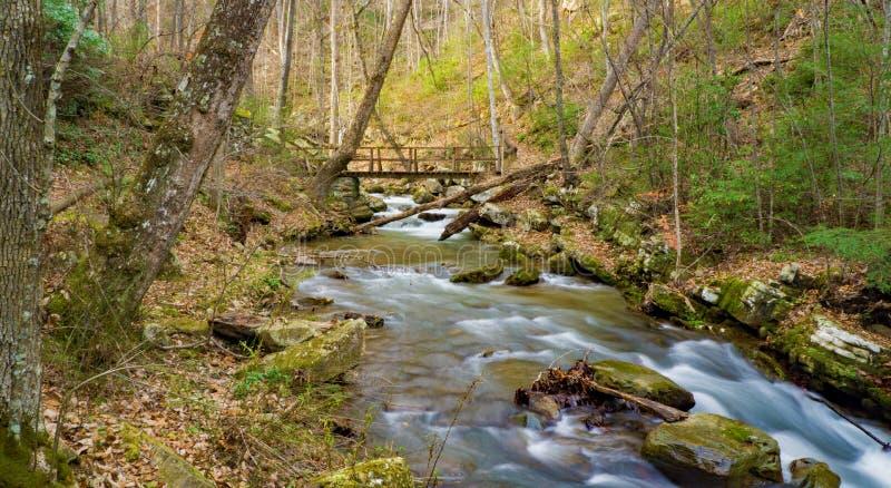 Später Autumn View eines Stegs über dem Brüllen des Laufnebenflusses lizenzfreie stockbilder