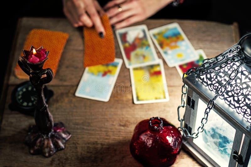 Spådomskonst på traditionella tarokkort på den gamla trätabellen med en lykta och en stearinljus arkivfoto