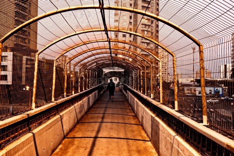 Spång över gångtunneldrevet av staden på skymning royaltyfri fotografi