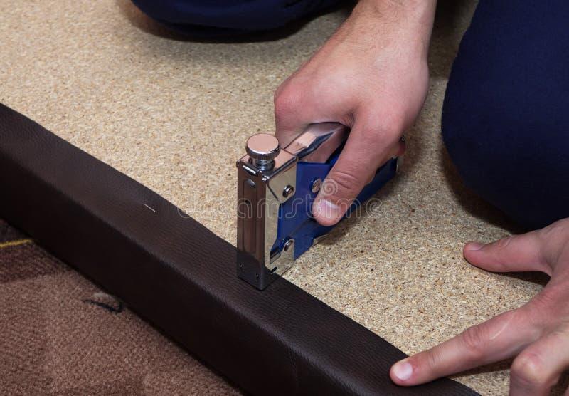 Spånskiva som stoppas med brunt läder Repairman som använder häftapparaten och häftklamrar royaltyfri fotografi