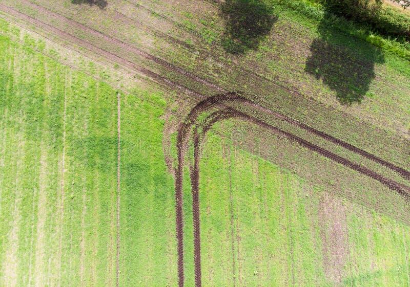 Spår av en traktor på ett fält som har gjort en vänd, när nå fältgränsen, abstrakt begreppeffekt vid vertikal flyg- sikt, till arkivbilder