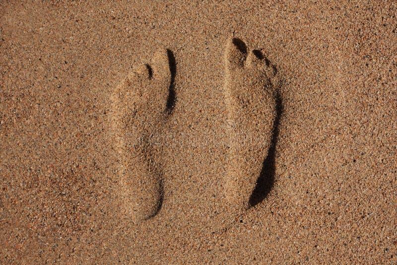 Spår av mänsklig fot i sanden arkivfoton