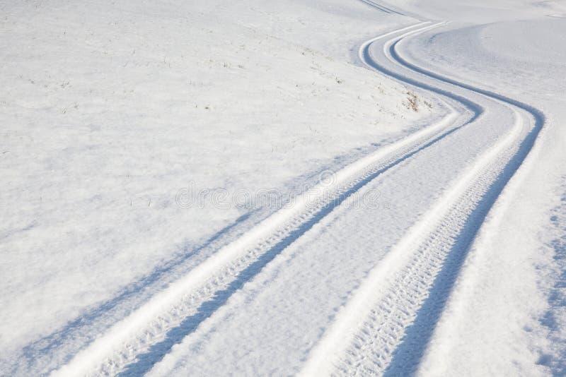 Spår för bilgummihjul på vintervägen royaltyfri fotografi