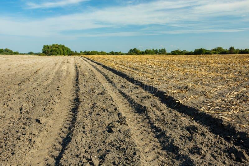 Spår på en jordbrukstraktor på ett plöjt fält arkivfoton