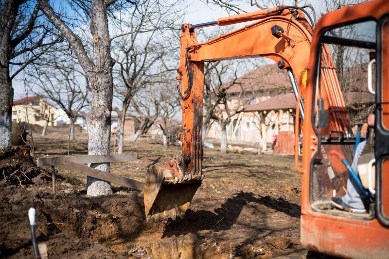 Spår-typ laddargrävskopa som gräver husfundamentet arkivfoto