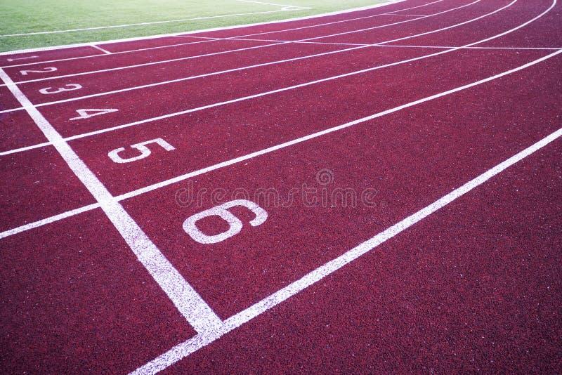 Spåra spring, röd trampkvarn i sportfält arkivfoto