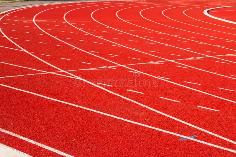 Spåra spring, röd trampkvarn i sportfält royaltyfri fotografi