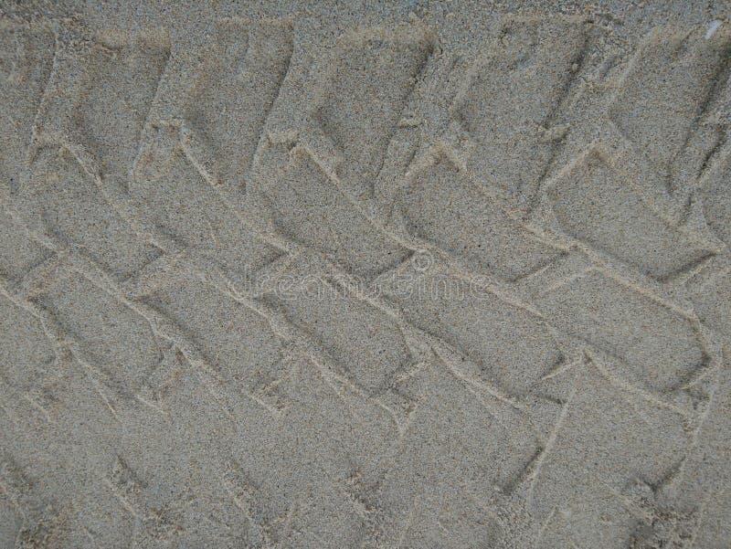 Spårar av hjul som kör på sanden som en bärgningsbil arkivfoto