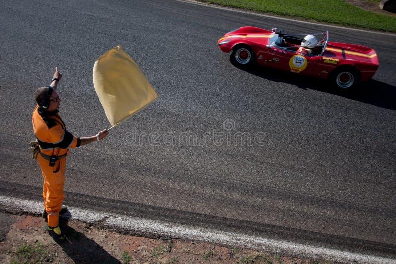Spårmarskalk som vinkar den gula flaggan arkivfoto