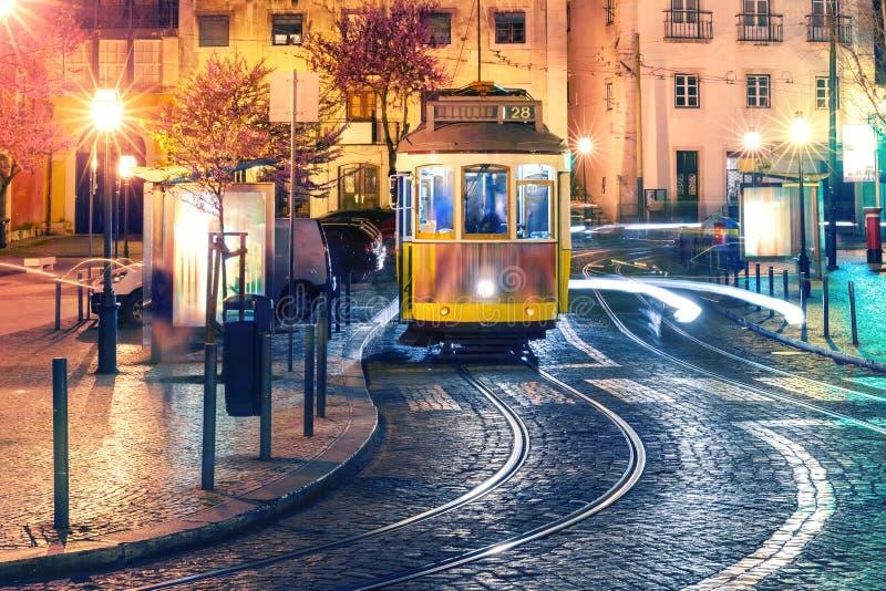 Spårvagn för guling 28 i Alfama på natten, Lissabon, Portugal royaltyfri bild