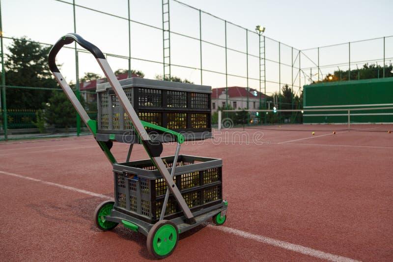 Spårvagn för tennisbollar på tennisbanan i aftonen royaltyfria foton